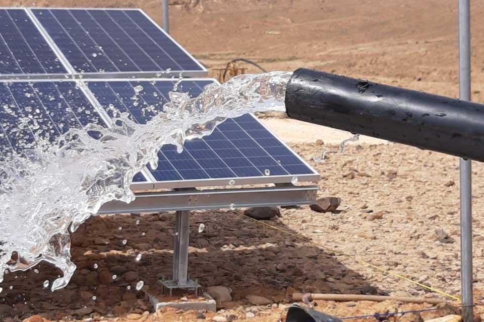 A pipe with flowing water and a solar panel in a development project in Yemen.
